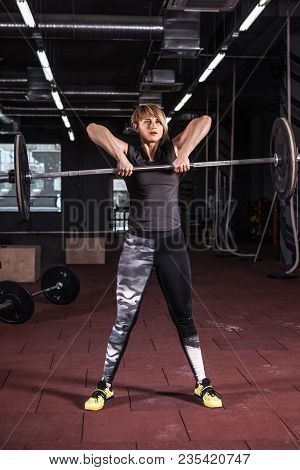 Strong Woman Lifting Barbell. . Fit Young Woman Lifting Heavy Weights At Gym.