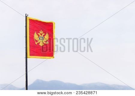 The Flag Of Montenegro (red, With The Two-headed Eagle Coat Of Arms In The Middle, And Golden Border