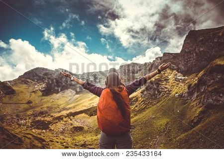 Photo of woman with backpack against background of picturesque mountain landscape
