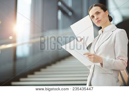Scowling businesswoman with financial documents expressing misunderstanding of some points