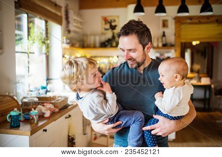 Father Holding Two Toddlers At Home. Paternity Leave.