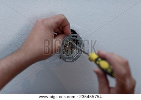 Electrician Man Installing New Electrical Switches Using Pliers During The Renovation Of The House