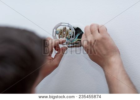 Electrician Installing New Electrical Switches Using Pliers During The Renovation Of The House