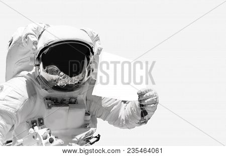 Astronaut Close Up Holding A Blank Sheet Of Paper. Spaceman In Outer Space. Elements Of This Image F