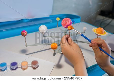 Kid Painting The Earth On A Solar System Model