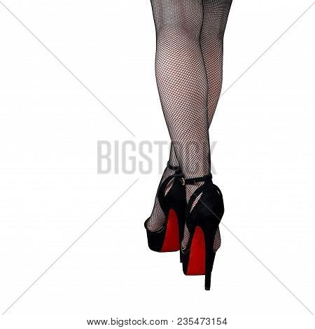 Female Legs In Stockings And High-heeled Shoes With A Red Sole. White Isolated Background.
