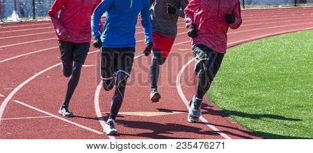 High School Boys Run A Workout Together Wearing Gloves And Spandex On A Red Track During Winter Trac