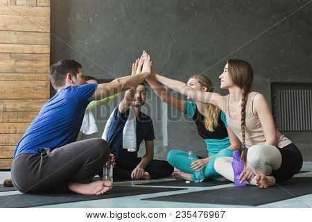 Young Men And Women Sitting In Circle With United Hands, Giving High Five Before Training. Togethern