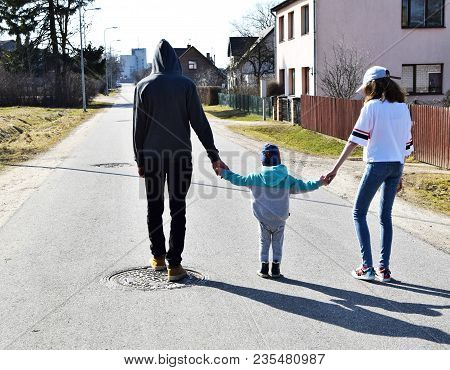 Teen Brother And Sister With Their Cute Little Two Years Old Baby Brother Are Walking Together In St