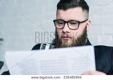 Selective Focus Of Focused Businessman In Eyeglasses Reading Newspaper
