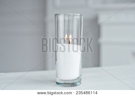 A Burning Candle In Tall Glass Vase Flask Standing On The Table Indoor.