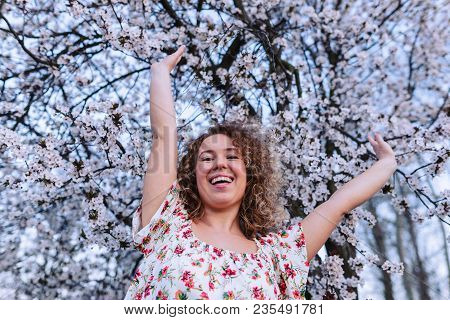 Beautiful Curly Woman Enjoying Smell Flowering Near The Cherry Tree.