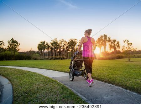 Beautiful, fit women walking and jogging outdoors along a paved sidewalk in a park pushing a stroller at sunset