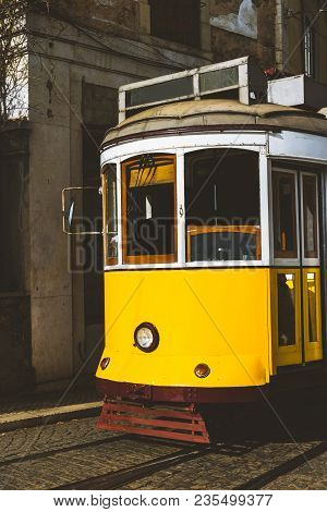Quaint Yellow Tram On The Rails Of Old And Beautiful Street Of Alfama District Of Lisbon. City Touri