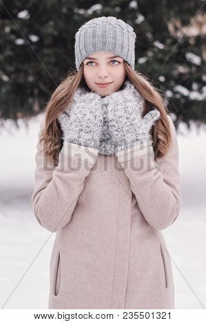 Vertical Portrait Of A Female Teenager In Warm Clothing: Beige Coat, Knitted Scarf, Mittens And Hat.