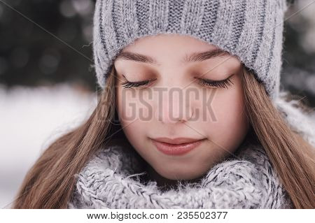 Portrait Of Female Teenager With Long Hair, In Knitted Hat And Scarf Of Gray Color Looking Down. Bea