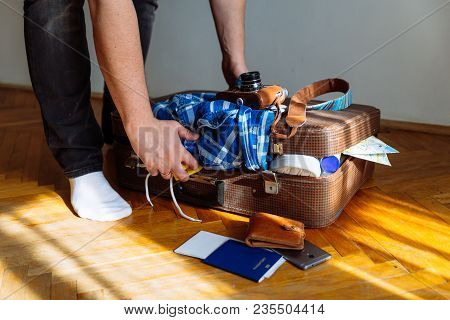 Travel Concept. Man Put Stuff In Suitcase. Overloaded Bag With Clothes