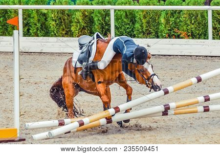 Young Rider Falling From Horse During A Competition. Horse Show Jumping Accident. Equestrian Sport B