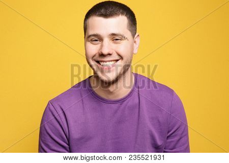 Portrait of young man with pierced eyebrow on color background