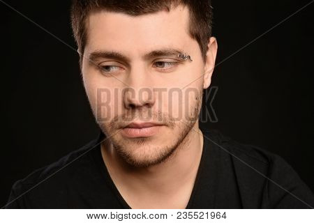 Young man with pierced eyebrow on black background