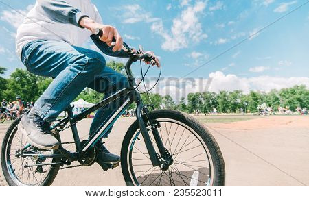 Hipster's Husband Rides A Bike In Sunny Summer Weather. Walking In The Park On A Bike. Close-up Bike
