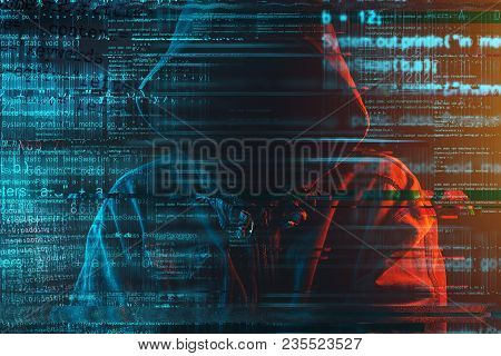 Stereotypical Image Of Computer Hacker With Hoodie And Computer Code. Faceless Hooded Male Person Li