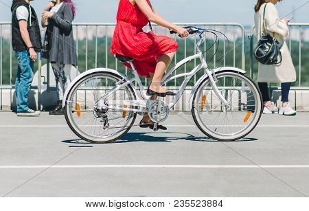 Lady On A Bike. The Girl In The Red Dress Riding A Bike Around The City. A Bicycle Ride In The City
