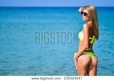 Beautiful Fit Young Woman In Sexy Yellow Bikini At The Beach. Girl In Swimsuit And Sunglasses, Summe