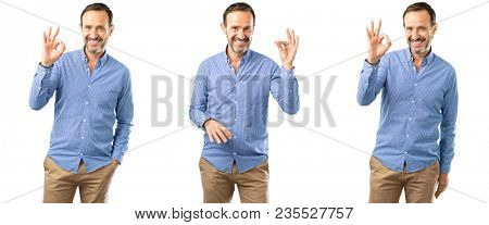 Middle age handsome man doing ok sign with hand, approve gesture over white background