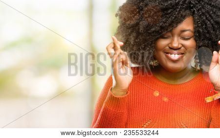 Beautiful african woman with crossed fingers asking for good luck, outdoor