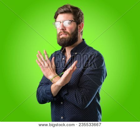 Young hipster man with big beard annoyed with bad attitude making stop sign crossing hands, saying no, expressing security, defense or restriction over green background