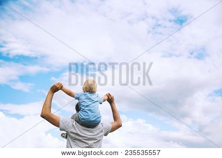 Father Carrying His Son On His Back With Raised Arms Up Against The Sky. Man And Child Boy. Family B