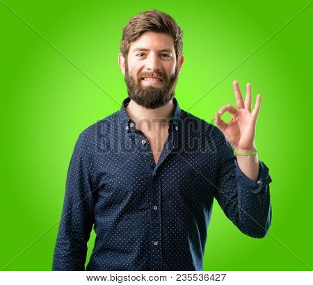Young hipster man with big beard doing ok sign with hand, approve gesture over green background