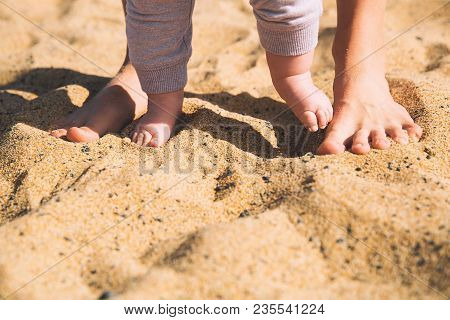 Parent And Child Walking Barefoot. Mother And Cute Little Baby Feet On Summer Beach Sand. Family On