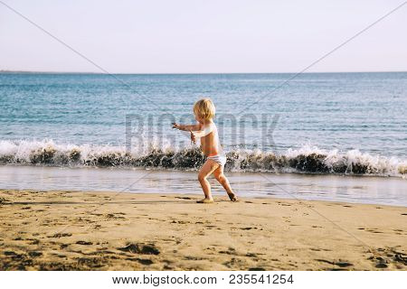 Happy Child Have Fun In The Sea Beach. Kid Play At The Ocean. Boy Running At Sea Shore. Summer Vacat