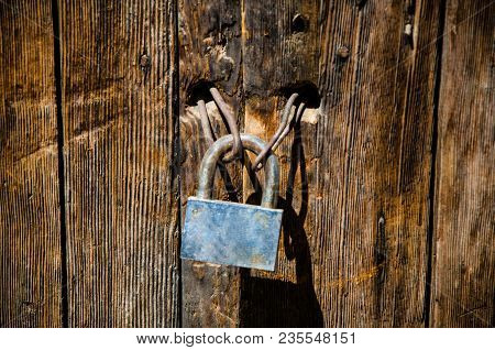 Occident Padlock On An Old Deteriorated Door