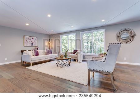 Spacious White Living Area With Hardwood Floor.