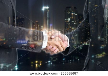 Double Exposure Business People Shaking Hands With View Night Time Of The City.