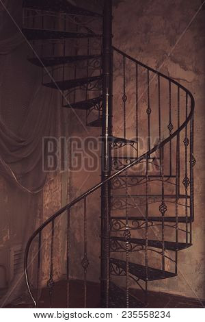 metal spiral staircase against the old wall background