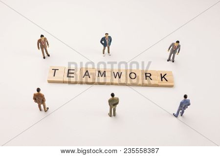 Miniature Figures Businessman : Meeting On Teamwork Word By Wooden Block Word On White Paper Backgro