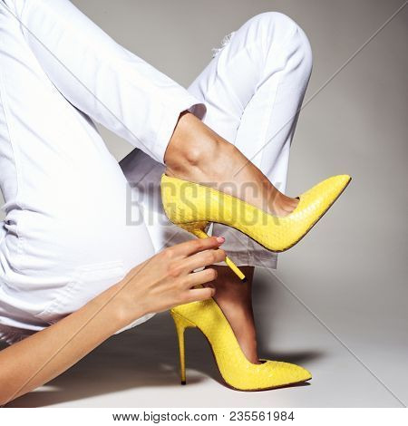 Closeup photo of female style leather bag. Part of women legs in beautiful fashionable yellow high heels.
