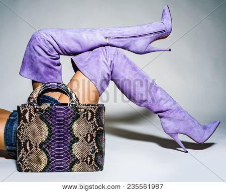 Closeup photo of female style leather bag. Part of women legs in beautiful fashionable batford high heels.