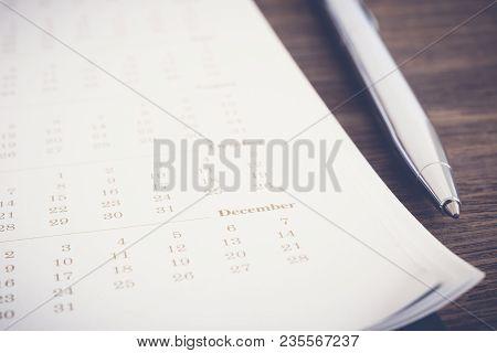 Closeup Calendar Pages Focus On December Month, Blurred Dates Pass, Modern Pen Put Beside On Wooden