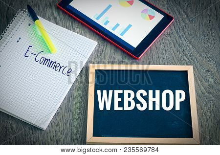 Plate With The Inscription Webshop And E-commerce  With A Tablet Graphs And Statistics And Block To