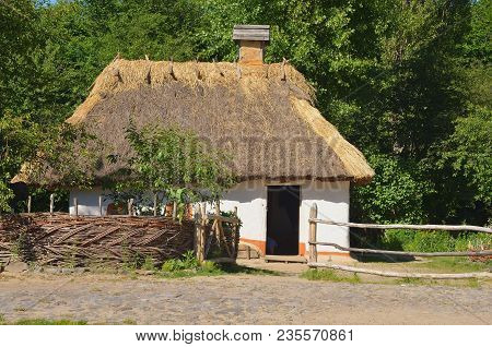 Wooden Old Ukrainian House In The General Plan, Behind The Essay. Green Summer