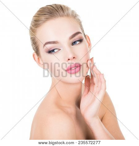 Young beautiful woman with health face. Beauty treatment concept. Skin care. Pretty girl with fresh skin of body. Young female touches cheek by fingers.