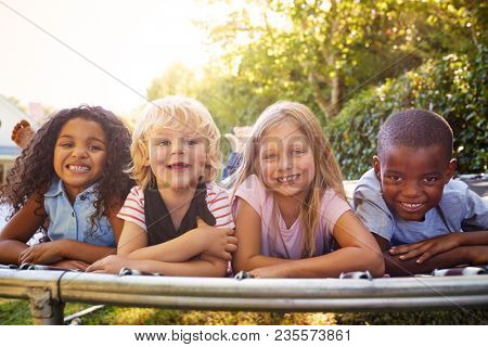 Four kids lying down together on a trampoline in the garden