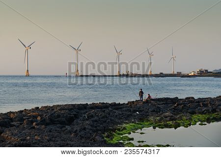 Jeju, Korea - May 25, 2017: Seascape Of Sinchang Windmill Coast With Fisherman, A Famous Place For D