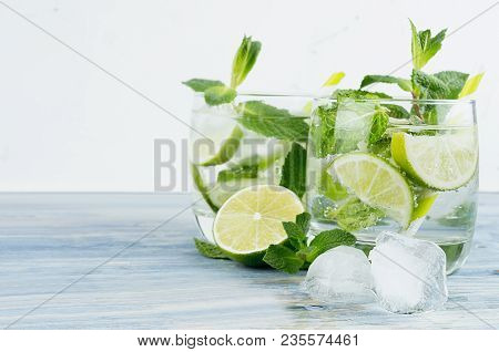 Fresh Cold Summer Beverage Gin And Tonic With Lime, Leaf Mint, Straw, Ice Cubes, Soda On Light  Whit
