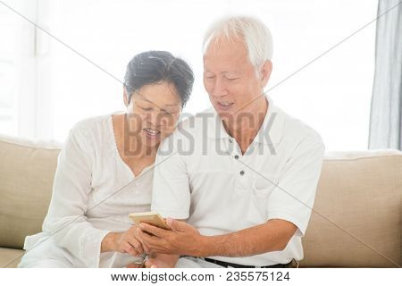 Portrait of happy Asian elderly couple using smart phone at home, old senior retired people indoor lifestyle.